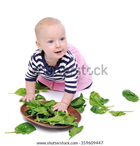 baby spinach studies/charming baby is exploring green spinach leaves; Isolated over White Background