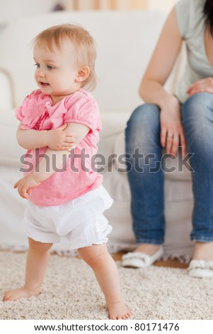Baby standing on a carpet while her mother is sitting on a sofa in the living room - stock photo
