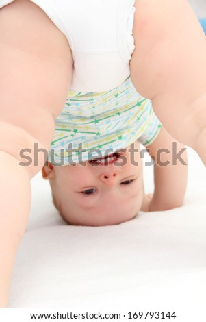 baby standing on head - stock photo