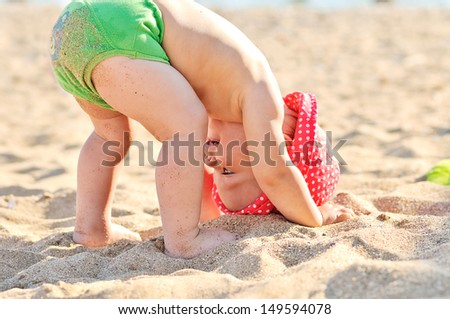 baby standing upside down on the beach
