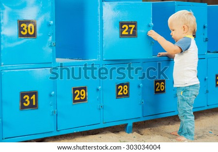 Baby stays near safety boxes - stock photo