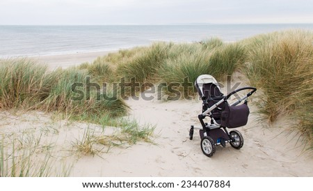 Baby stroller standing at a beach in the Netherlands - stock photo