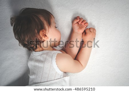 Baby sweet sleeping on a white bed background. Newborn sleep. Concept of baby care