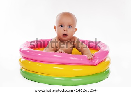 Baby swimming in kid inflatable pool, isolated on white background