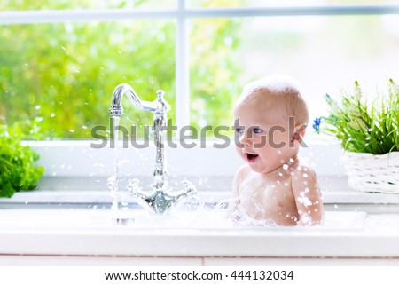 Baby taking bath in kitchen sink. Child playing with foam and soap bubbles in sunny bathroom with window. Little boy bathing. Water fun for kids. Hygiene and skin care for children. Bath room interior - stock photo