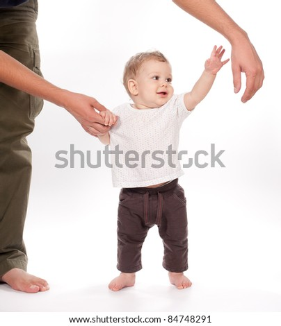 baby taking first steps with father help on white background - stock photo