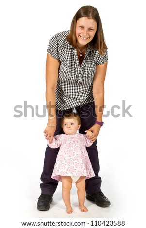 baby taking first steps with mother help on white background - stock photo