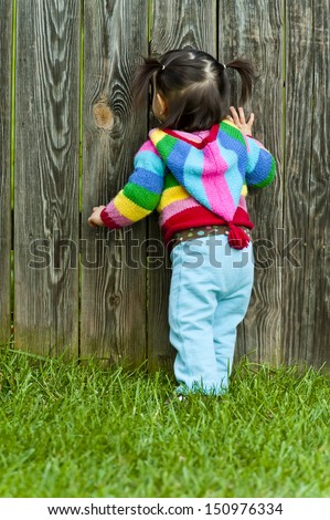 Baby toddler girl peeping through fence hole - stock photo