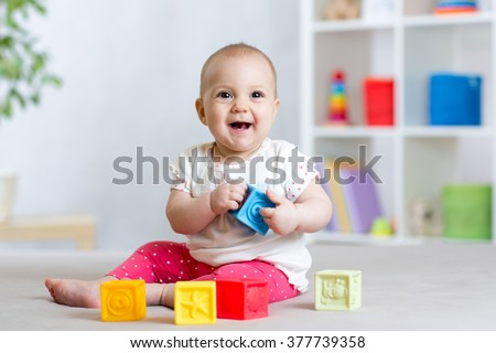 baby toddler playing color toys at home or nursery - stock photo