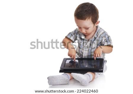 Baby toddler pointing and looking at a digital tablet on his lap, isolated on white - stock photo