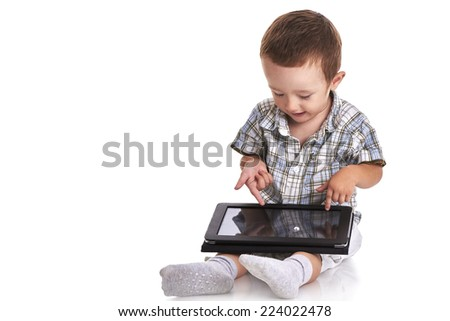 Baby toddler pointing and looking confused at a digital tablet on his lap, isolated on white - stock photo