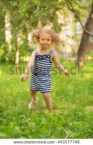 Baby toddler running on green lawn near the house.