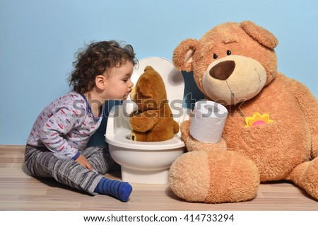 Baby toddler sitting on the floor near a potty and kissing a teddy bear. Cute kid potty training for pee and poo helped by teddy bear who gives him toilet paper - stock photo