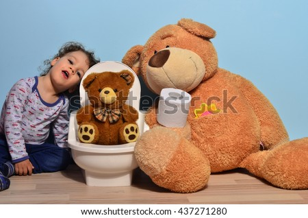 Baby toddler sitting on the floor near a potty with a small teddy bear on it. Cute kid potty training for pee and poo helped by teddy bear who gives him toilet paper - stock photo