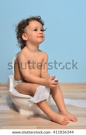 Baby toddler sitting on the potty and playing with toilet paper. Cute kid potty training for pee and poo - stock photo