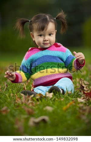 Baby toddler wearing colorful clothing and sitting on grass in fall season.