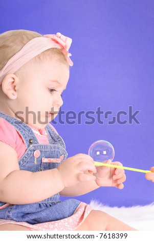 baby touching a bubble - stock photo
