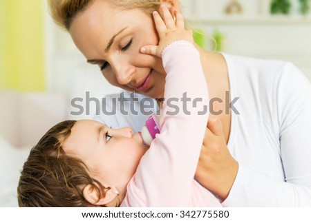 Baby touching mom's face while drinking a milk from  bottle.Shallow doff - stock photo