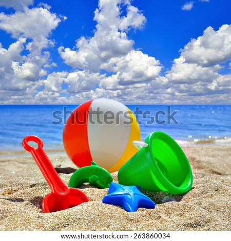 Baby Toys on beach sand against the blue sky - stock photo