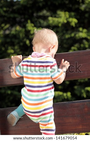 Baby trying to force the fence - stock photo