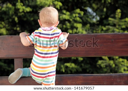 Baby trying to go through the fence