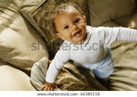Baby trying to stand - stock photo