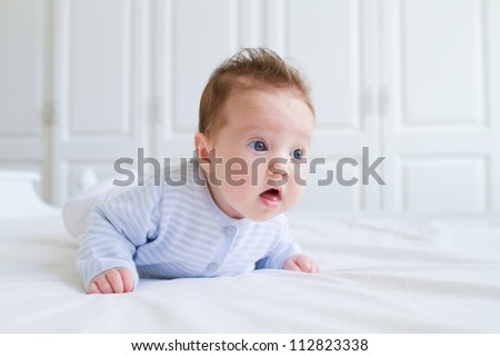 Baby tummy time, wearing blue clothes in a white nursery - stock photo