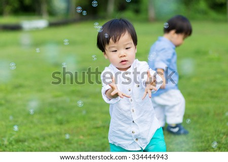 Baby twins playing outdoor