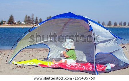 Baby under a beach shelter