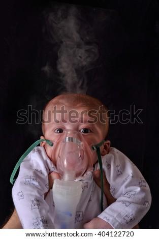 Baby using medical respiratory inhalator mask vapor seam treatment for flu  - stock photo