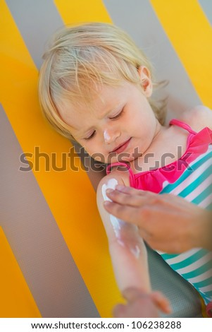 Baby waiting while mother applying sun block creme on arm - stock photo