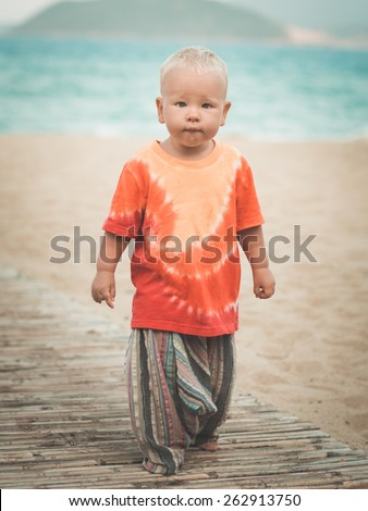 Baby walking along the beach - stock photo