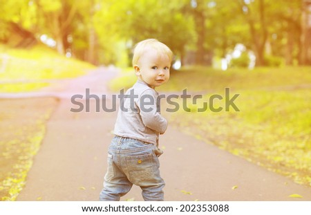 Baby walking in summer park - stock photo