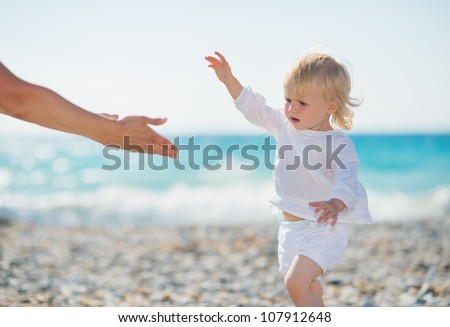 Baby walking to mothers outstretched hands - stock photo