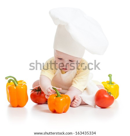baby wearing a chef hat with healthy  food vegetables - stock photo