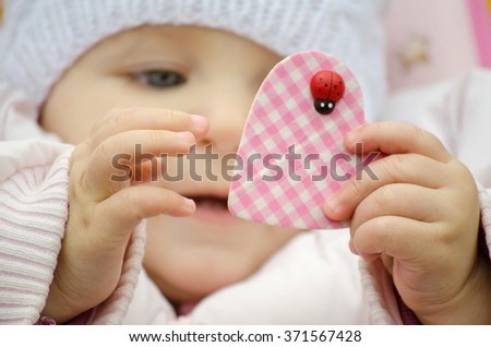 baby wearing a hat holding a heart - stock photo