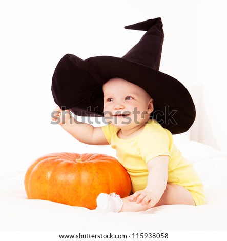 baby wearing a witch's hat with a big  pumpkin, in bed at home