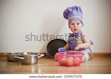 Baby wearing chief hat playing with kitchen tools - stock photo