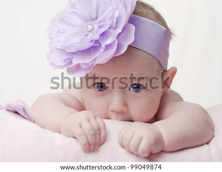 Baby wearing purple bow - stock photo