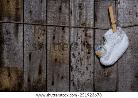Baby white sock with a clothespin on a wooden background - stock photo
