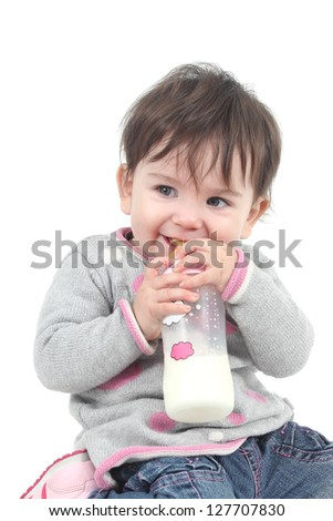 Baby with a feeding bottle in her mouth on a white isolated background