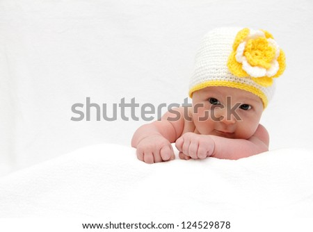 Baby with a knitted white hat baby on stomach - stock photo
