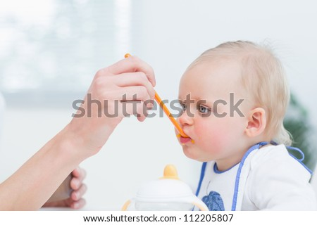 Baby with a plastic spoon on his mouth in living room