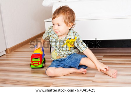 baby with a toy car on the floor at home - stock photo