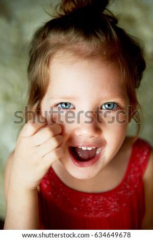 Baby with a tuft on the head,with blue eyes and playful smile
