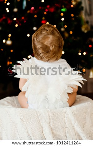 baby with angel wings on the background of Christmas tree garland
