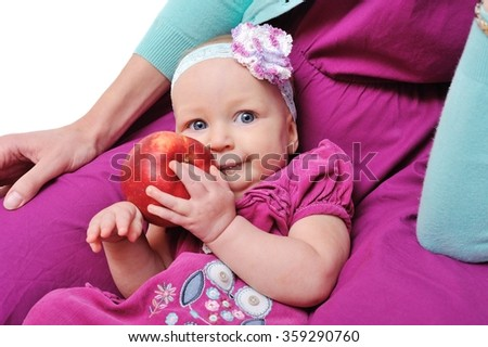 Baby with apple in the hands of mother/charming baby with red apple sits on hands at mum; Isolated over White Background - stock photo