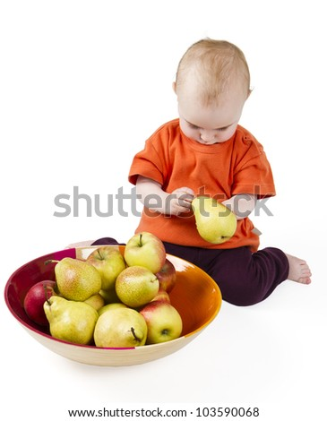 baby with apples and pears laying in bowl - studio shot