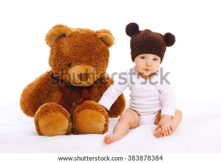 Baby with big teddy bear toy on white background - stock photo