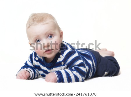 baby with blue eyes lying looking at camera, white background